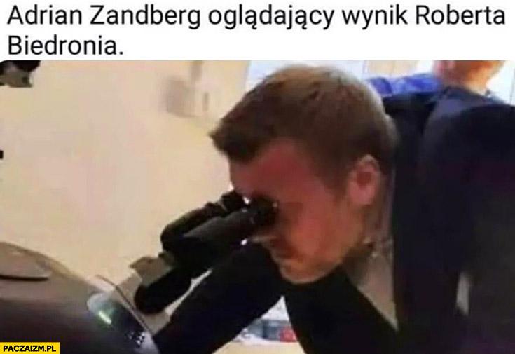 Adrian Zandberg oglądający wynik Roberta Biedronia pod mikroskopem