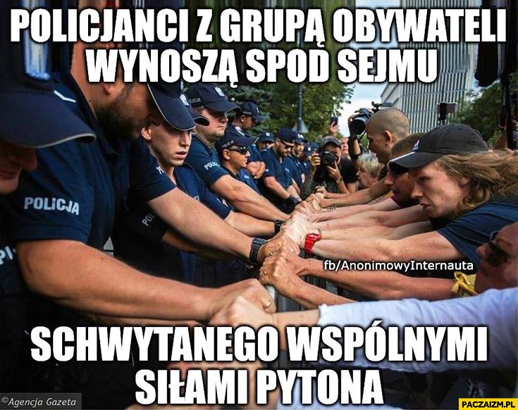 Policjanci z grupą obywateli wynoszą spod sejmu schwytanego wspólnymi siłami pytona trzymają barierki KOD Anonimowy internauta
